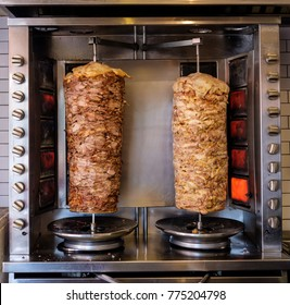 Two rotating skewered chicken and lamb meat grilled in stainless steel grill and ready to serve in a typical Middle Eastern fast food kebab sandwich