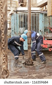 Two roughnecks do the equipment for fixing of rig pipe