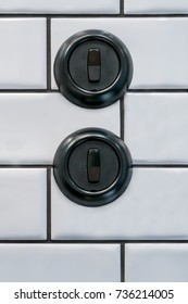 Two round black decorative bakelite light switches on white bathroom tile wall.