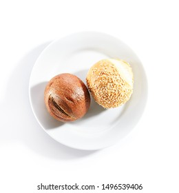 Two round buns of rye and wheat flour with sesame seeds top view. Small round brown bread roll and white gluten free bread roll on white restaurant plate isolated