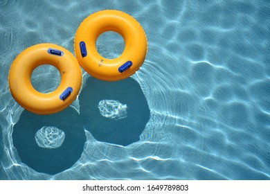 Two round inflatable yellow pool rings floating in a cool blue refreshing swimming pool.