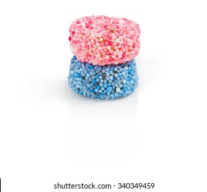 Two round liquorice allsorts candy isolated on white background. One pink and one blue.
