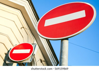 Two round red signs No Entry near old house