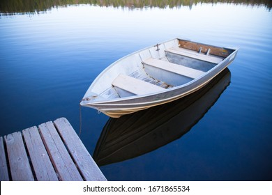 two rowboat floating in calm Sequoia lake next to deck with beautiful reflection of sky