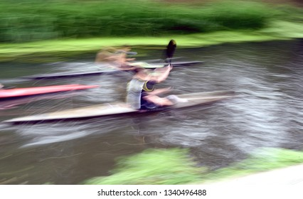 Two rowers moving at speed along a river with intentional blurred motion and rowing action on the waterway