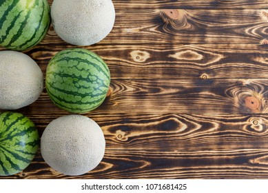 Two rows of alternating ripe melons with watermelons and cantaloupe, also known as sweet melon or spanspek, on decorative wood with copy space