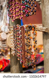 Two Rows of beautiful African bead necklaces hanging from wooden branches in an open air market