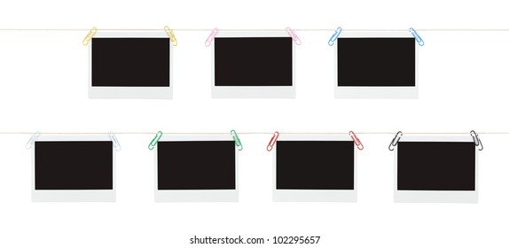 Two rows of blank pieces of instant film hanging from colorful paperclips on strings isolated on white.