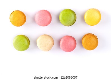 Two rows of colorful French macarons isolated on white. Top view with copy space.
