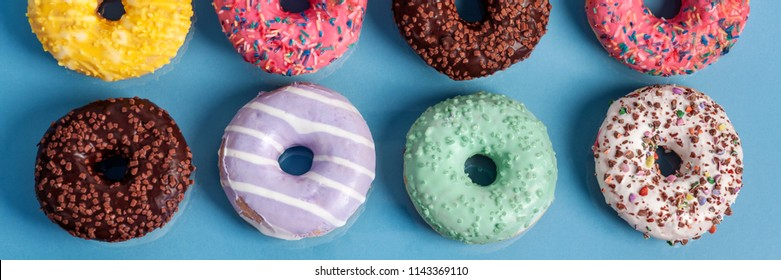 Two rows of donuts with sprinkles and icing on a panoramic blue background