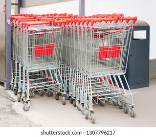Two rows of empty shopping carts with red handle under a shelter.