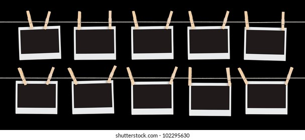 Two rows of five blank pieces of instant film held on strings with  clothespins isolated on black.