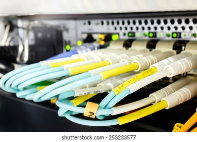 Two rows of multiple fiber cables plugged into a fiber switch, with green activity lights, and standard fiber labelling.