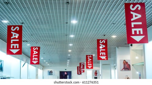 two rows of red vertical sale posters with white letters hang from grid ceiling in big shop in sale season. sale poster board at fashion clothes shopfront