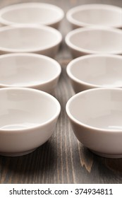 Two rows of white ceramic bowls close up macro shot, vertical. Selective focus