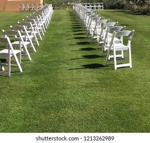 Two rows of white chairs on a lawn