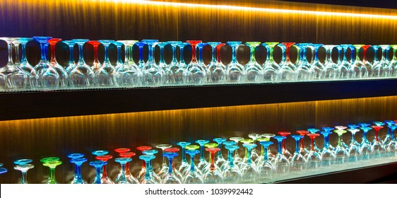 Two rows of wine glasses with multi-coloured stems