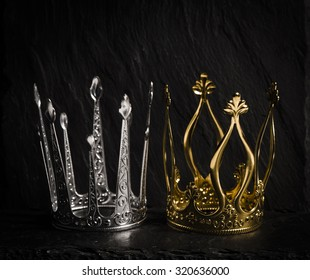 Two royal crowns on dark stone surface. Concept of wealth, success and kingdom.