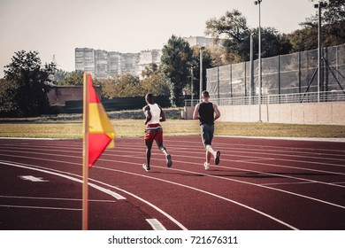 Two runners actively enter the turn runs through the stadium