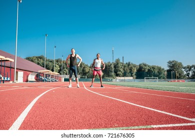 Two runners against the blue sky at the stadium are warming up