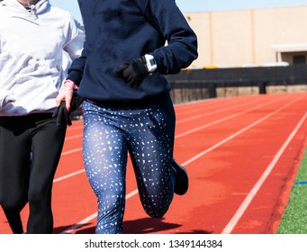 Two runners close up training on a track wearing blus and black spandex and blue and white sweatshirt carrying their gloves.