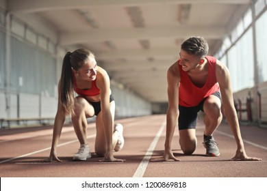 Two runners are getting ready to run on the track.