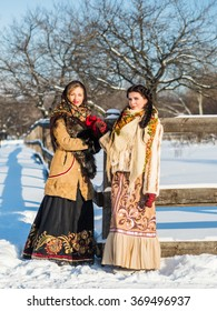Two Russian boyar in Russian national costumes in the dead of winter in a village near the fence