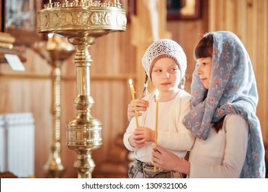 two Russian girls in a scarf on their heads stand in an Orthodox Church, lights a candle and prays in front of the icon.