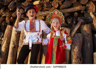 Two Russian kids in russian folk costume boy and girl dancing together and emotionally smiling