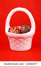 two russian tradition easter eggs in white porcelain basket over red