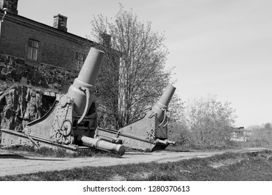 Two rusted cannons in front of a military building on Suomenlinna island, Finland. A total of 100 stand on the sea fortress - monochrome processing