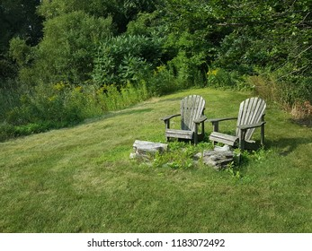 Two rustic adirondack chairs next to a pile of wood with a forest in the background.