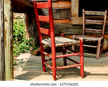 Two rustic chairs on a wooden front porch of a cabin