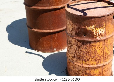Two rusty steel drums with one showing a puncture hole