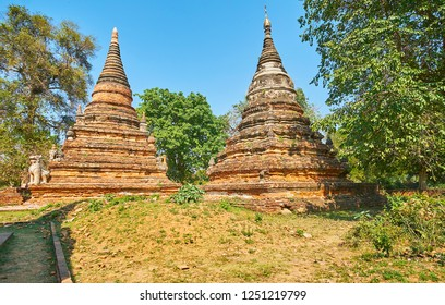 Two rusty-red stupas of Daw Gyan Pagoda decorated with relief belts and preserved sculptures, Ava (Inwa), Myanmar.