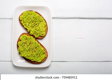 Two rye toast bread with smashed green avocado with lime juice and black pepper on top on a white plate and wooden background.