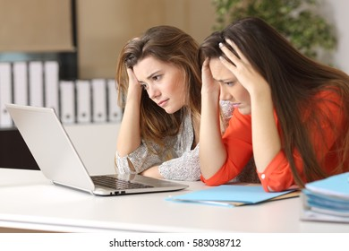 Two sad coworkers reading bad news on line in a laptop on a desktop in an office indoor