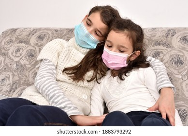 Two sad and depressed sisters sitting on the sofa with medical protective face masks. Older sister hugging her younger sister.