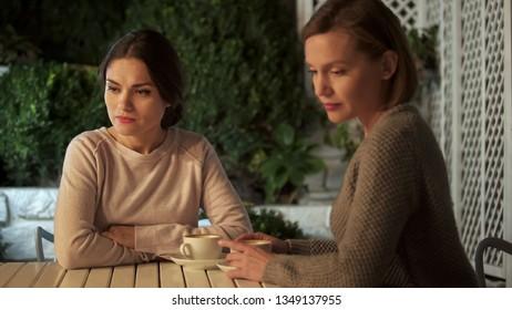 Two sad ladies sitting outdoors after quarrel, communication problem, conflict