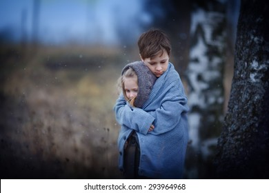Two sad little embracing children in the field on a cool spring evening. Kids in the country