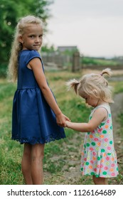 Two sad little sister standing holding hands