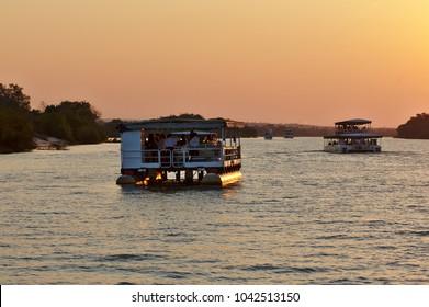 Two safari ships cruising Zambezi river at sunset. Victoria Falls, Zimbabwe Africa.