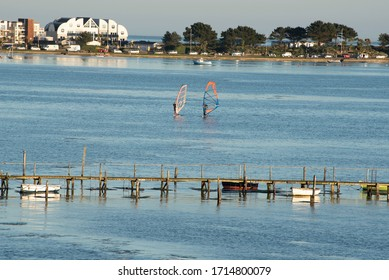 Two Sailboarders in blue sea with old jetty at Sandbanks, Poole Dorset.  Beautiful Poole Bay is a Mecca for watersports with its stunning coastline and Sandbanks is a millionaires playground.