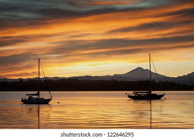 Two sailboats anchor off of Lummi Island in the Puget Sound area of western Washington State. The snow capped Mt. Baker is in the background.
