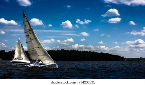 Two sailboats in the match racing regatta at the sunny day - yachting sport
