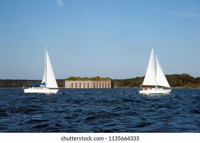 Two sailboats pass by an old stone fort in open water in Casco Bay, Maine.