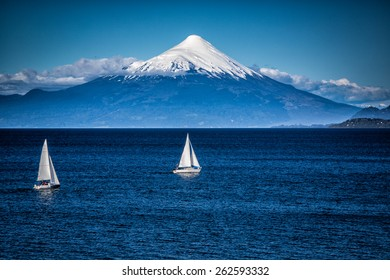 Two sailboats sail in front of snow capped Orsono Volcano in Chile-Edit