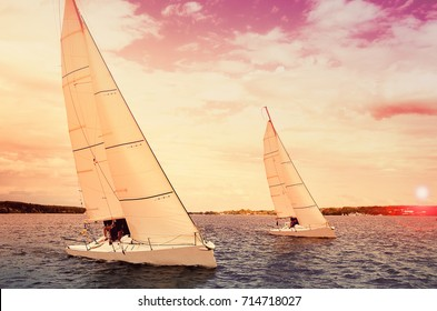 Two sailboats at sunset. Sailing yacht race, regatta. Recreational Water Sports, Extreme Sport Action. Healthy Active Lifestyle. Summer Fun Adventure. Hobby
