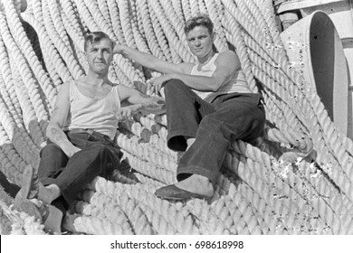 Two sailors resting on ropes