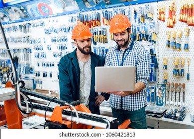 Two salesmen in construction helmets are discussing equipment selection near woodworking machine in power tools store.